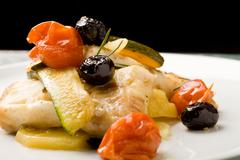 Baked cod with olives and tomatoes Stock Photos
