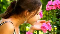 Beautiful girl smelling pink flowers in the garden Stock Footage