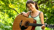 Beautiful girl with an acoustic guitar outdoors Stock Footage