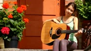 Beautiful girl with her guitar near flowers outdoors Stock Footage