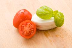 Tomatoe and mozzarella on cutting board Stock Photos