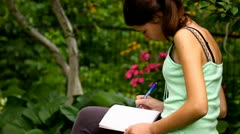 Girl writing into her notebook in the park Stock Footage