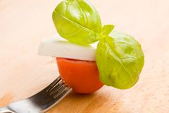 fork with tomatoe and mozzarella - stock photo
