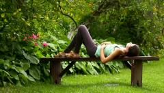 Girl lying down, sleeping on the bench in the garden - stock footage