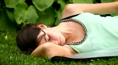 Young girl sleeping on the grass in the park, lying down Stock Footage