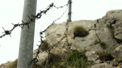 Barbwire fence on mountain Stock Footage
