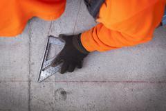 Construction worker marking cement Stock Photos