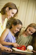 Hispanic family cooking together - stock photo