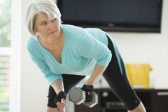 Caucasian woman exercising with hand weights Stock Photos