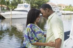 Mixed race couple hugging near waterfront Stock Photos