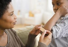 Black mother putting bandage on son's elbow Stock Photos