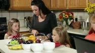 Mom cutting fruit for kids Stock Footage