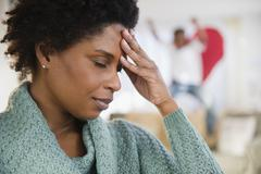 Black woman with headache and playful son in background - stock photo