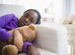 Musta tyttö makaa sohvalla nallekarhu Kuvituskuvat