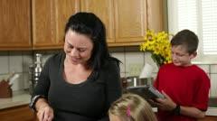Äiti työskentelee keittiössä lasten kanssa Arkistovideo