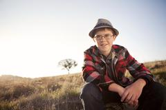 Caucasian boy sitting in remote field - stock photo