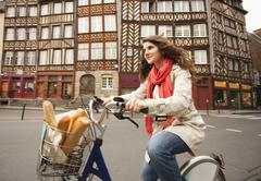 Caucasian woman riding bicycle with bread in basket - stock photo