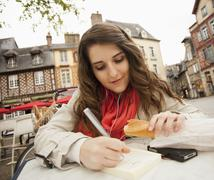 Caucasian woman eating bread and writing in book - stock photo