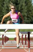 Caucasian runner jumping over hurdles Stock Photos