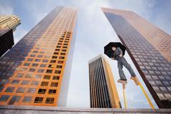 Caucasian businesswoman walking on stilts in urban environment - stock photo