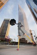 Caucasian businesswoman walking on stilts in urban environment Stock Photos
