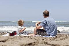 Caucasian father and son eating on beach Stock Photos