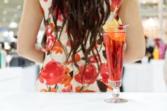a glass of cocktail and a girl - stock photo
