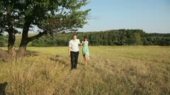 Young couple walking on the yellow grass - stock footage