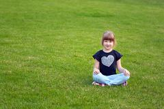 Young smiling girl sitting on a grass Stock Photos