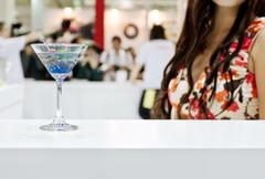 a glass of blue laguna cocktail with a sexy girl on background - stock photo