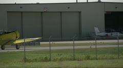 Aircraft, harvard taxi through frame past hangar Stock Footage
