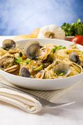 pasta with clams on blue background - stock photo