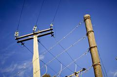 barbed wire power line - stock photo
