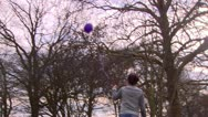 Girl releasing purple balloon into sky in park Stock Footage