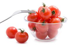 Ripe tomatoes in glass bowl isolated Stock Photos