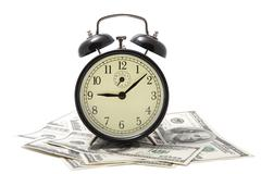 Alarm clock over heap of money isolated Stock Photos