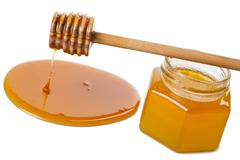 Stock Photo of wooden dipper with honey and bottle isolated