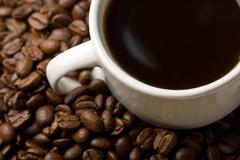white cup of coffee and coffee beans - stock photo
