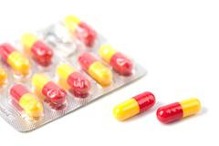 red and yellow capsule pills in blister isolated - stock photo