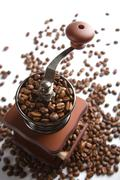 Old-fashioned coffee grinder and roasted coffee beans isolated Stock Photos