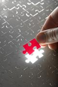 Hand holding red puzzle piece Stock Photos