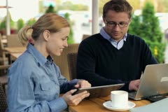 Businesspeople working with laptop and tablet in cafe, stedycam shot Stock Footage