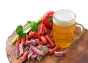 Stock Photo of mug of beer and an assortment of salami and vegetables on a cutting board