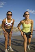 Hispanic female runners racing at beach Stock Photos