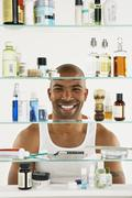 African American man looking in medicine cabinet - stock photo