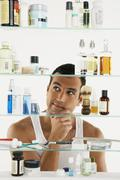 Hispanic man looking in medicine cabinet - stock photo