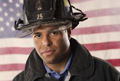 Hispanic male firefighter in front of American flag Stock Photos