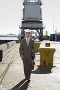 Asian businessman walking on commercial pier Stock Photos