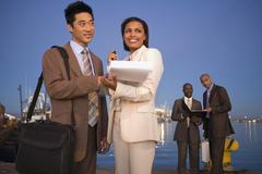 Multi-ethnic businesspeople on commercial pier Stock Photos