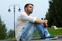 young tired man sit on border in summer park - stock photo